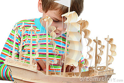 Boy work with zeal on hull of artificial boat