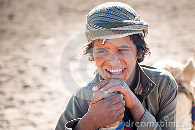 Boy working with camels in Bedouin village on the desert Editorial Stock Image