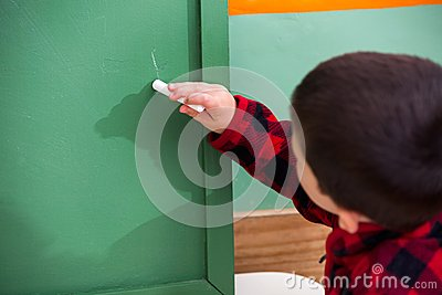 Boy Writing On Green Chalkboard In Preschool