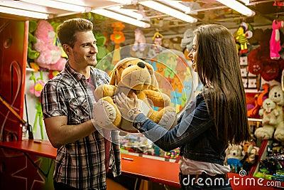 Boyfriend giving gift his girlfriend on amusement park