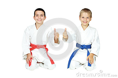 Boys athletes sit in a ritual pose karate and point the finger super