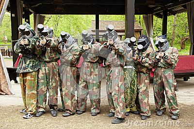 Boys in camouflage stand with paintball guns