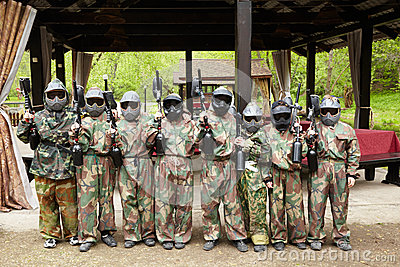Boys in camouflage suits with paintball markers