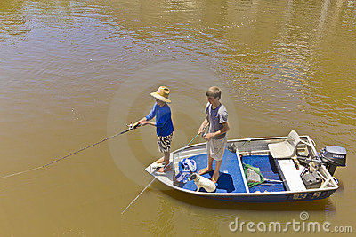 Boys and dog fishing in boat in flooded river. Editorial Photography