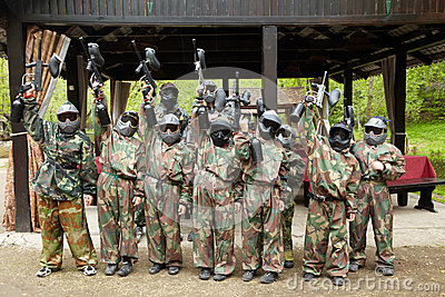 Boys dressed in camouflage stand on paintball base
