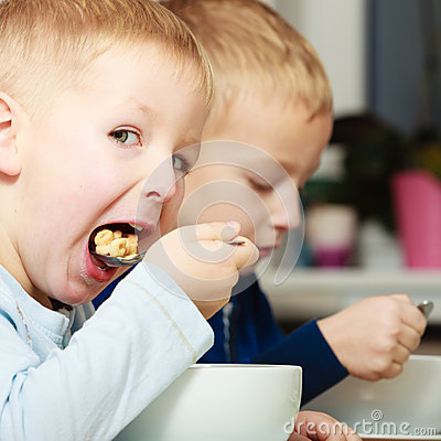 Free Boys Kids Children Eating Corn Flakes Breakfast Meal At The Table Stock Images - 39379744