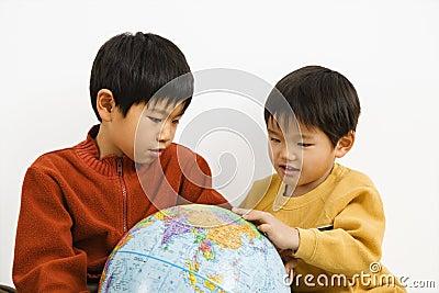 Boys looking at globe