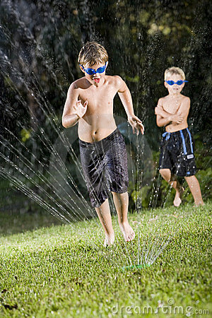Boys playing with lawn sprinkler