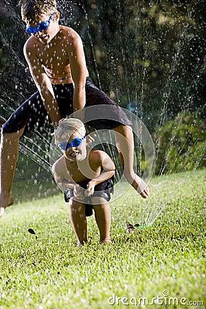 Boys playing leapfrog over lawn sprinkler
