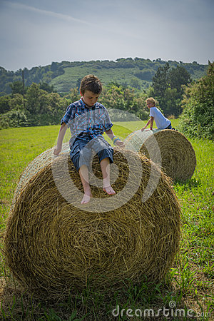 Boys on round hay bales