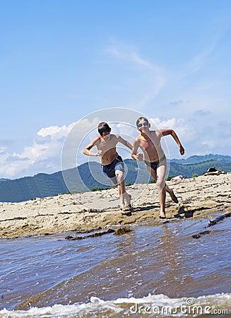 Boys run in water