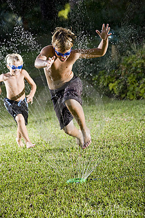 Boys running fast through lawn sprinkler