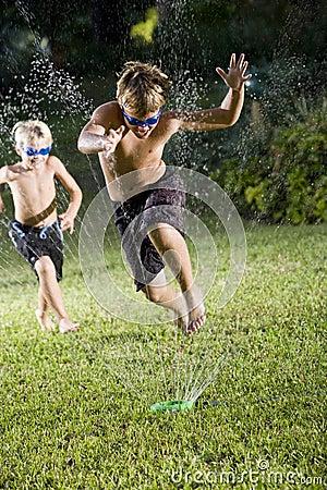 Free Boys Running Fast Through Lawn Sprinkler Royalty Free Stock Photos - 16753778