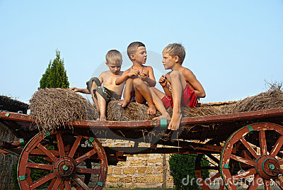 Boys sitting on a hay bale on sky background