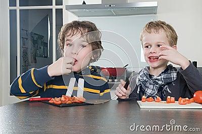 Boys tasting tomato