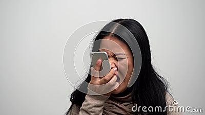 Boze Aziatische vrouw die op haar telefoon gillen stock footage