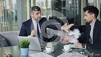 Boze zakenman tearing documenten die bij partner tijdens besprekingen in koffie werpen stock videobeelden