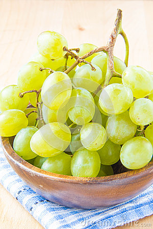 Branch of green fresh grapes in a wooden bowl