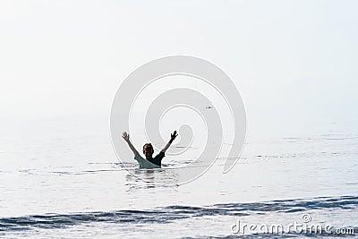 Braços do menino da nadada levantados