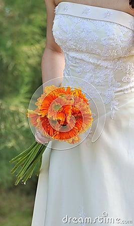 Braut im weißen Hochzeitskleid mit Blumenstrauß