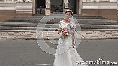 Braut in langen Kleidern steht am Eingang des Operntheaters stock video footage