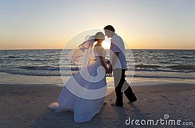 Braut-u. Bräutigam-Paar-küssende Sonnenuntergang-Strand-Hochzeit