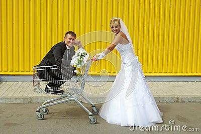 Braut und Bräutigam, die mit einem Korb des Supermarktes spielen