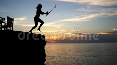 Brave girl jumping into the sea from a rock with go pro action camera  during beautiful sunset  slow motion  1920x1080