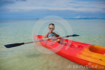 Brave little cute girl floating in a kayak on the