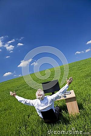 Brazos del hombre de negocios levantados en el escritorio en campo verde