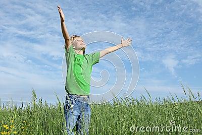 Brazos felices del niño levantados en rezo
