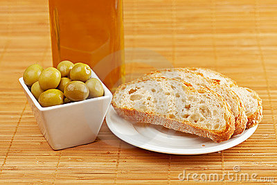 Bread, olive oil bottle and olives