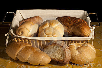 Bread in a wicker basket on a yellow tablecloth