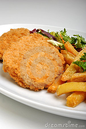 Breaded fish steak with salad on a plate