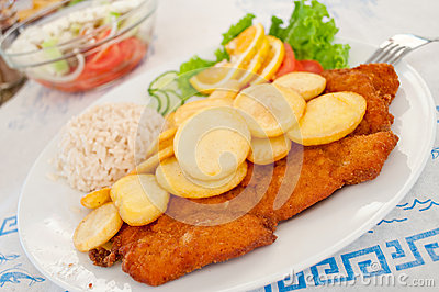 Breaded steak with potato and rice