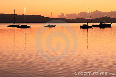 Boat silhouettes by golden sunrise