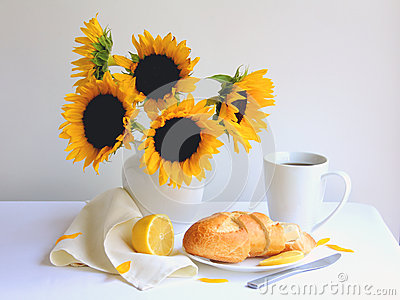Breakfast coffee with fresh bread and lemon on white tablecloth with beautiful sunflowers in white vase.