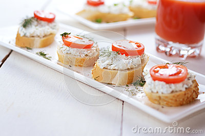 Breakfast of cottage cheese bruschettas and tomato juice