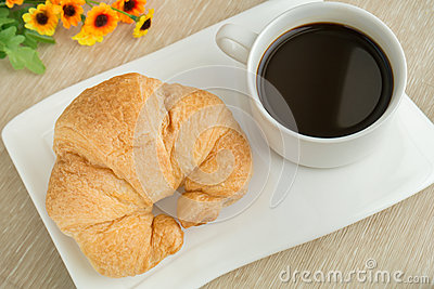 Breakfast with cup of black coffee and croissant