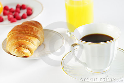 Breakfast. A cup of coffee and croissant