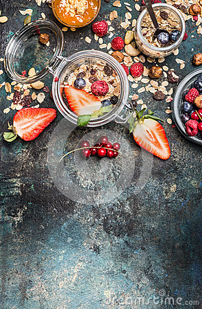 Free Breakfast In Jars. Muesli With Strawberries And Other Fresh Berries, Nuts And Seeds On Rustic Background Stock Image - 70333461
