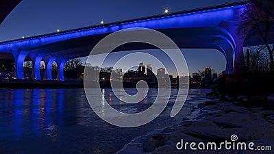 Brede hoekcityscape van Minneapolis van onder de iconische blauwe aangestoken 35W-Brug stock footage