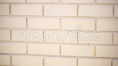 The brick wall is white. The camera moves slowly stock footage