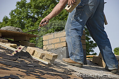 Bricklayer Mason Laying Chimney Bricks on House