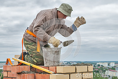 Bricklayer works on 15th floor of building editorial image image