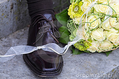 Bridal bouquet and groom s shoe