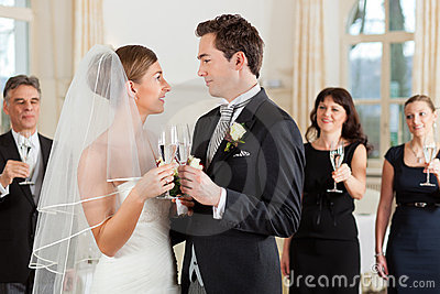 Bridal couple clinking glasses