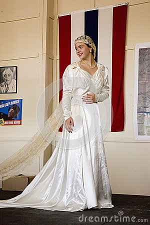 Bride in 1940s wedding dress posing in front of flag for Wedding dresses reading pa