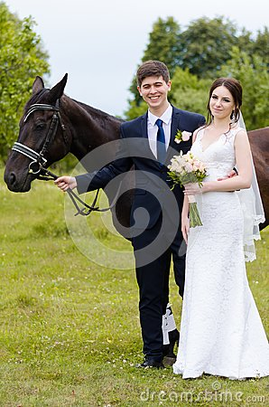 Free Bride And Groom Are Standing In The Park Near The Horse, Wedding Walk. White Dress, Happy Couple With An Animal. Green Background Royalty Free Stock Images - 102678149