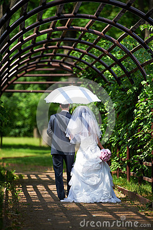 Free Bride And Groom Goes Along The Arch Stock Photo - 29927310